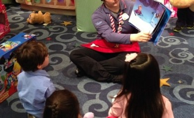 Tanayia reads a story to a group of children during storytime at Disney Store